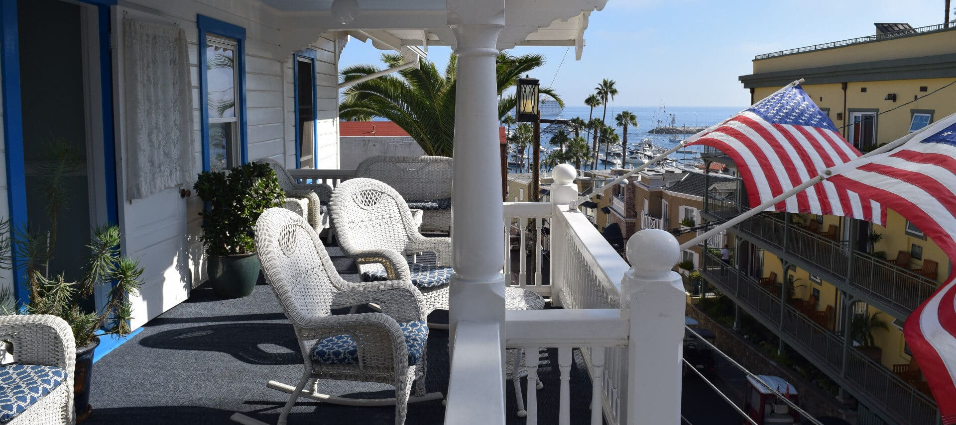 Second floor balcony with wicker rocking chairs an American flags overlooking ocean view.