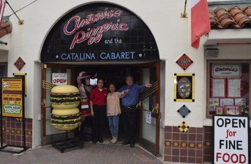 Three people smiling from entrance to a pizzaria