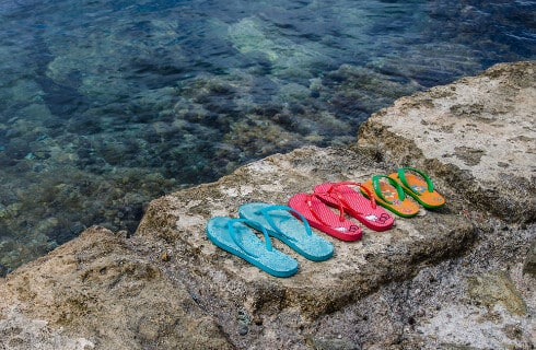Multi-colored flip flops on stone wall overlooking clear water.