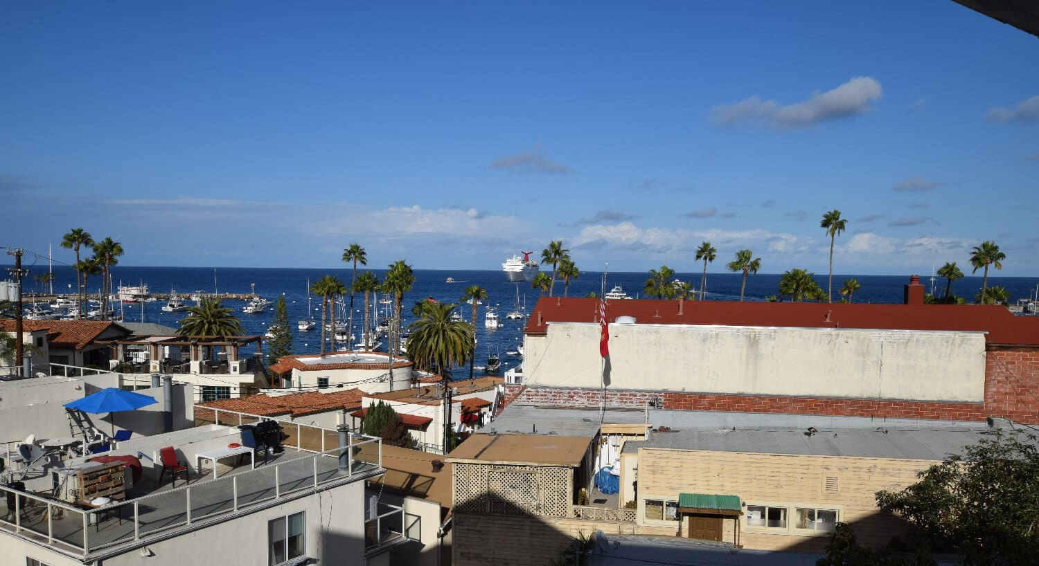 A view of the ocean over rooftops from the balcony of the Hotel Catalina