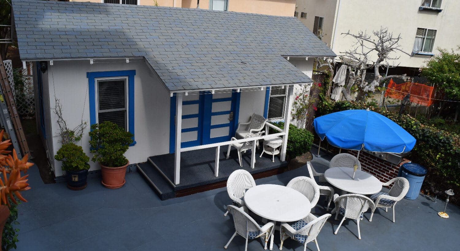Ecterior of white cottage with blue trim with white patio tables and chairs.