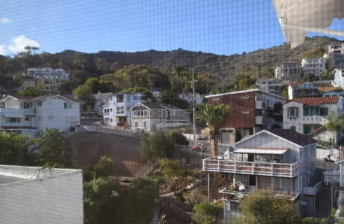 View of mountains with houses all around from behind a window screen.