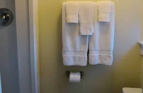 White towels on a towel rack in a bathroom.