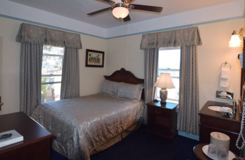 Queen bed in bedroom with two large windows and a ceiling fan
