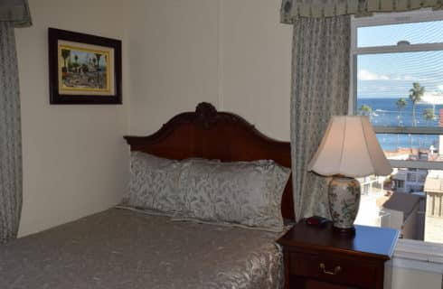 Queen bed in next to window with wooden headboard and nightstand