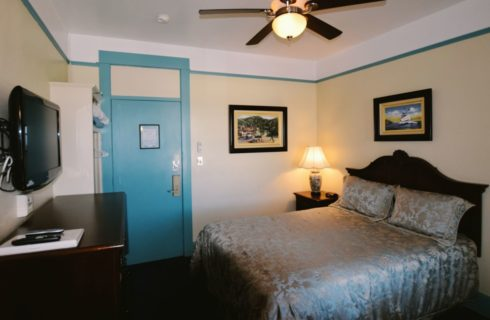 Room painted in pale yellow with blue trim holds a queen bed and a ceiling fan