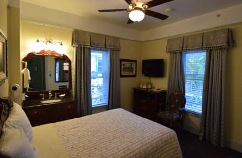 Room with queen bed, ceiling fan and two large windows with blackout curtains.