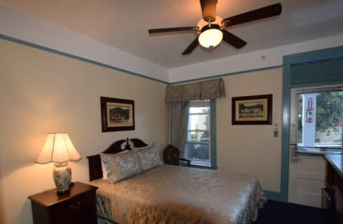 Bedroom with queen bed, wooden headboard an nightstand and a ceiling fan.