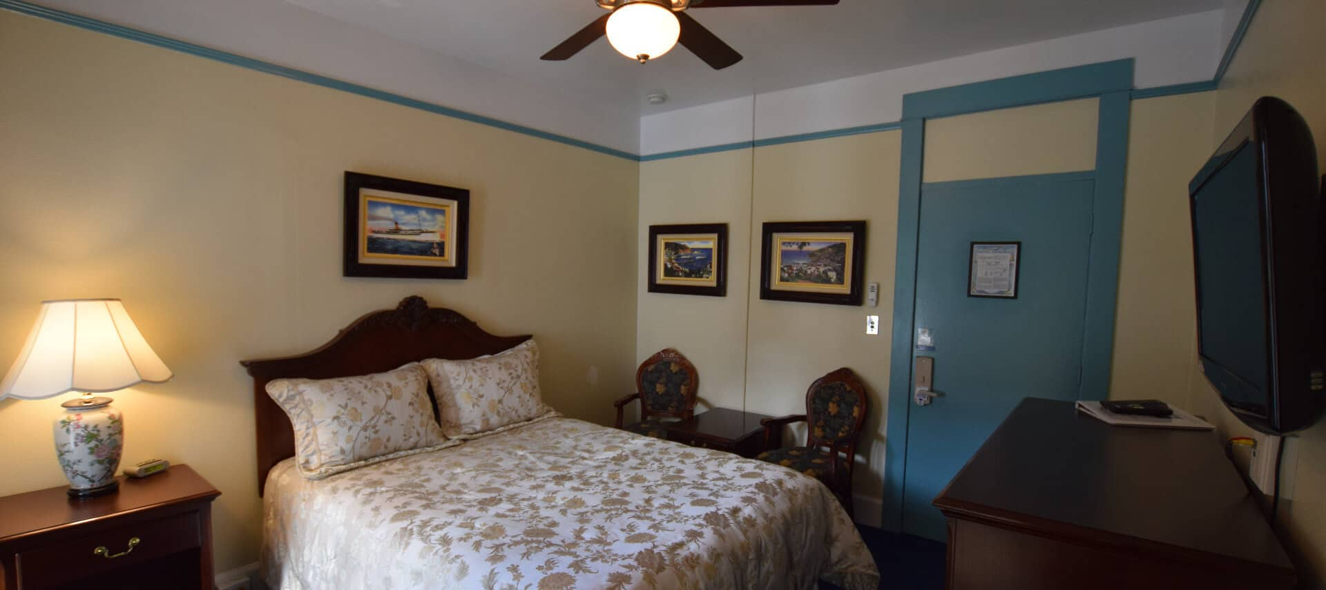 Room painted in yellow and bright blue with a queen bed and ceiling fan.