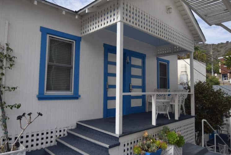 Quaint little cottage painted white with blue trim with a small front porch.