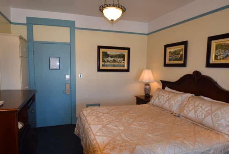 Room painted in pale yellow with blue trim holds a king bed and nightstand.