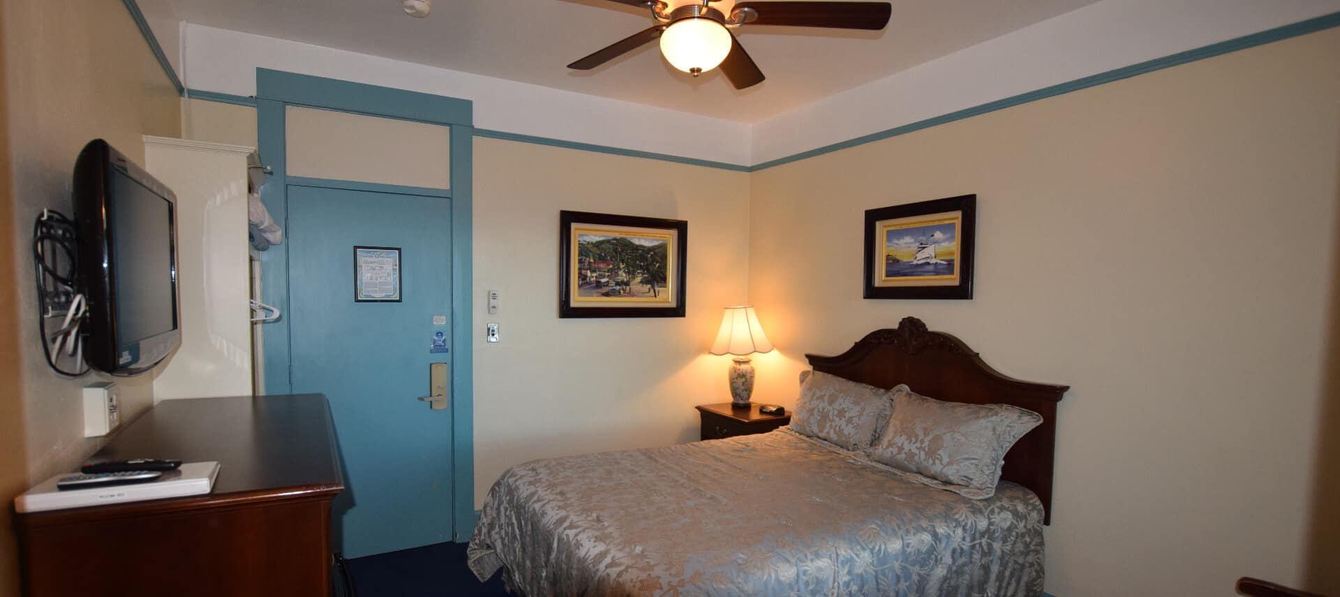 Room painted in pale yellow with blur trim holds a queen bed and a ceiling fan.