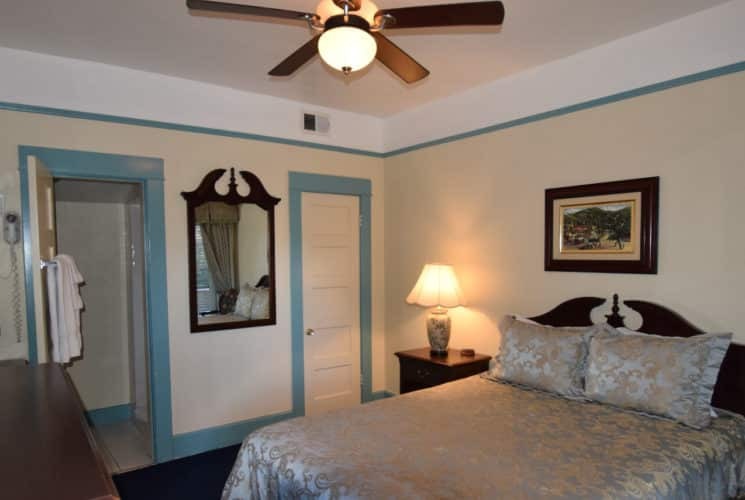 Bedroom painted white with blue trim holds a queen bed with a satin cover