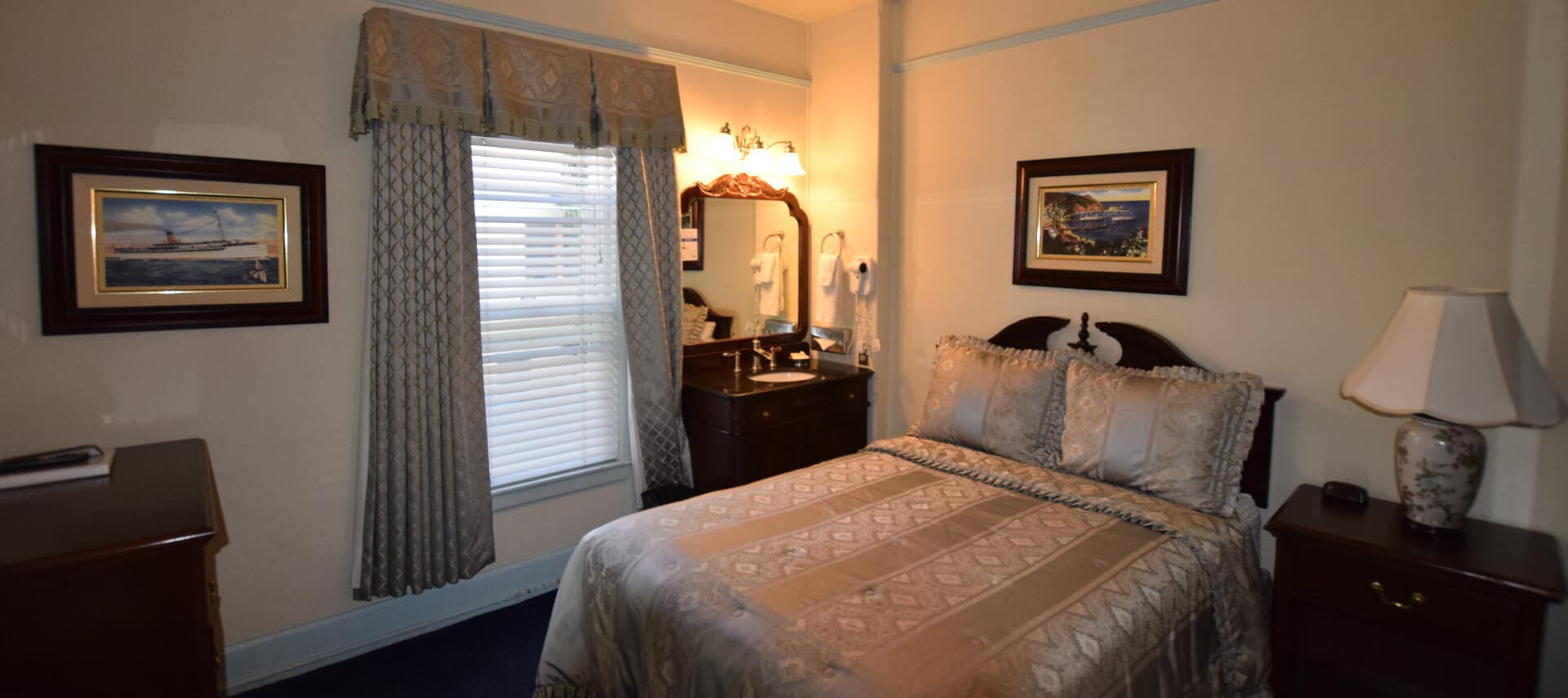 Bedroom with Queen bed, large window and antique dresser with mirror.